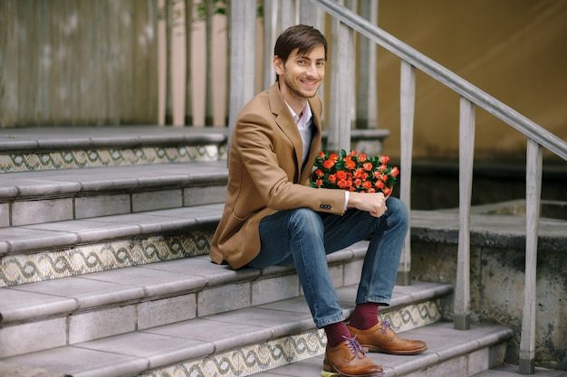 Красивый мужчина держит букет из роз, улыбаясь счастливым