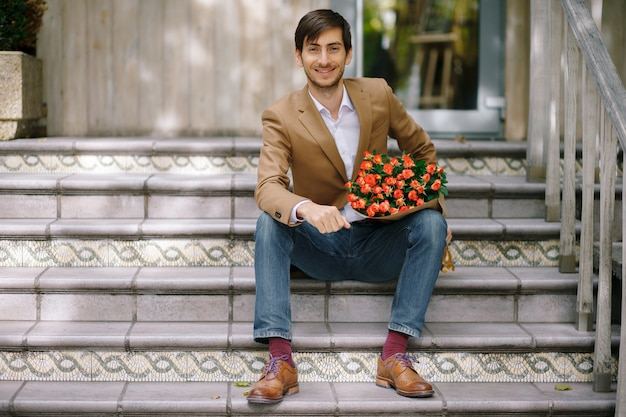 Handsome man holding bouquet of roses