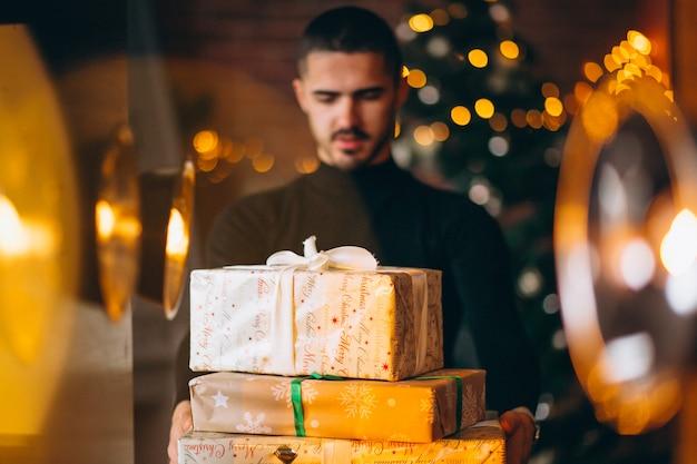 Красивый мужчина держит коробки рождественские подарки