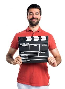 Handsome man holding a clapperboard