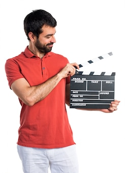 Handsome man holding a clapperboard