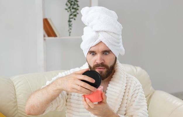 スキンスパボディと男性のコンセプトのためのスキンケアのための化粧品のピンクのスクラブを保持しているハンサムな男