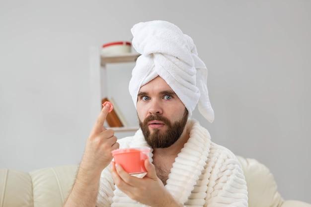 スキンスパボディと男のコンセプトのスキンケアのための化粧品ピンクスクラブを保持しているハンサムな男