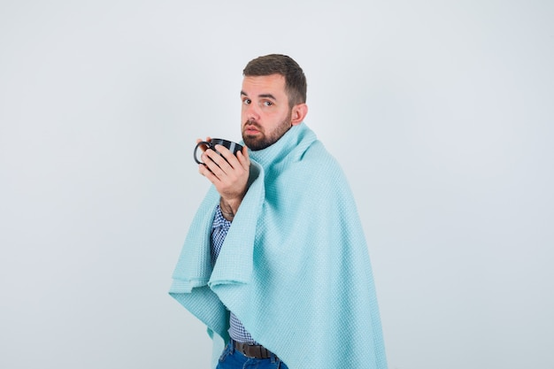 Handsome man holding cup of tea in both hands in shirt, jeans, shawl and looking exhausted. front view.