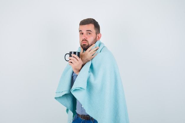 Handsome man holding cup of tea, having throat ache in shirt, jeans, shawl and looking exhausted , front view.