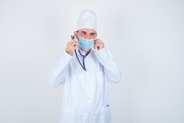 Uomo bello che tiene i pezzi dell'orecchio dello stetoscopio nelle orecchie come se stesse ascoltando in camice medico bianco, maschera e guardando felice, vista frontale.