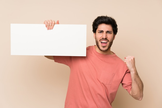 Handsome man holding an empty white placard for insert a concept