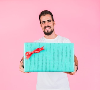 Handsome man holding gift box against pink background