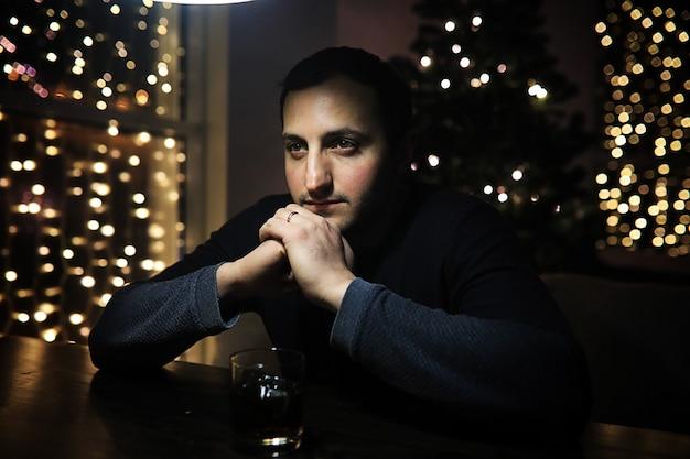 夜のクラブで氷とアルコールのガラスを保持しているハンサムな男