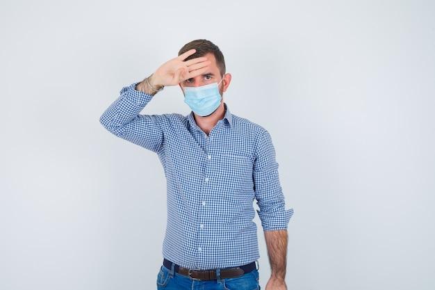 ハンサムな男が頭に手をつないで、シャツ、ジーンズ、マスクで体温をチェックし、疲れ果てているように見えます。正面図。