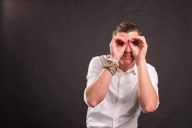 目の近くで手をつないで、コピースペースで黒い表面の上の眼鏡を模倣してハンサムな男