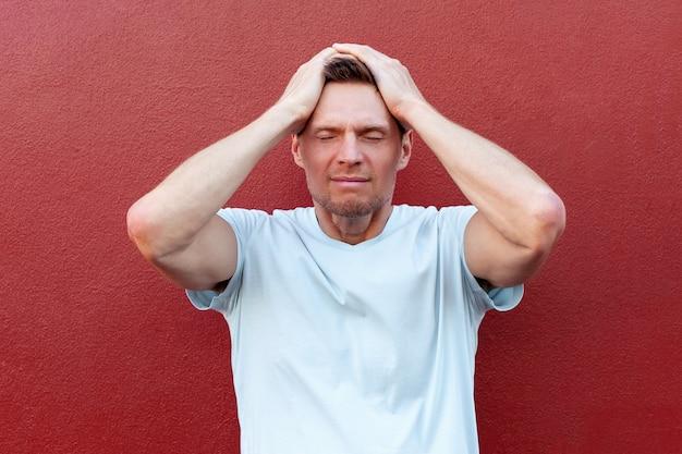頭痛とストレスを抱えている彼の頭に手を握ってハンサムな男感情と心理状態の概念色の背景