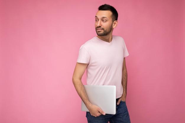 Красивый мужчина держит портативный компьютер, глядя в камеру в футболке на изолированном розовом фоне