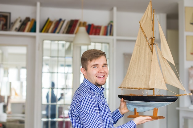 Handsome man holding layout of a sailboat