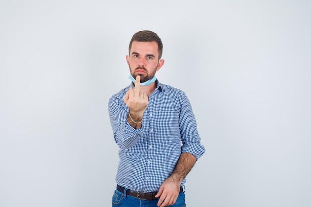 Uomo bello che tiene la maschera sotto il mento, mostrando il dito medio in camicia, jeans, maschera e guardando serio, vista frontale.