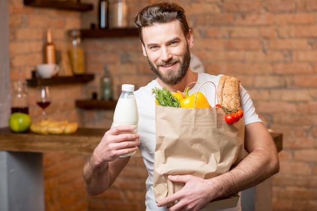 부엌에서 건강에 좋은 음식으로 가득 찬 종이 봉지에 우유를 들고 있는 잘생긴 남자