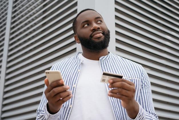 モバイルとオンラインショッピングを保持しているハンサムな男