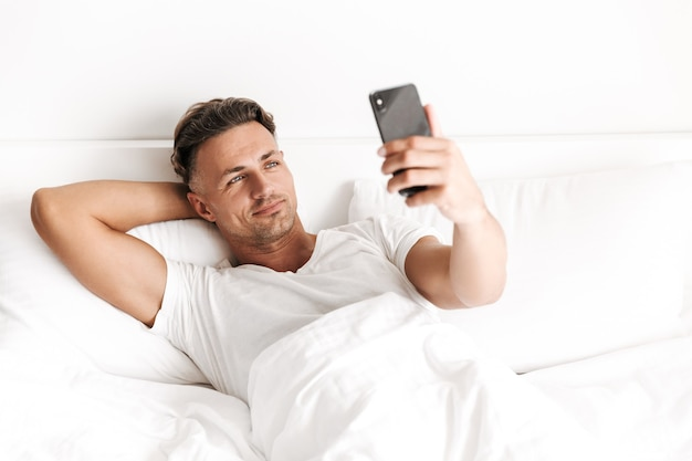 Красивый мужчина держит мобильный телефон