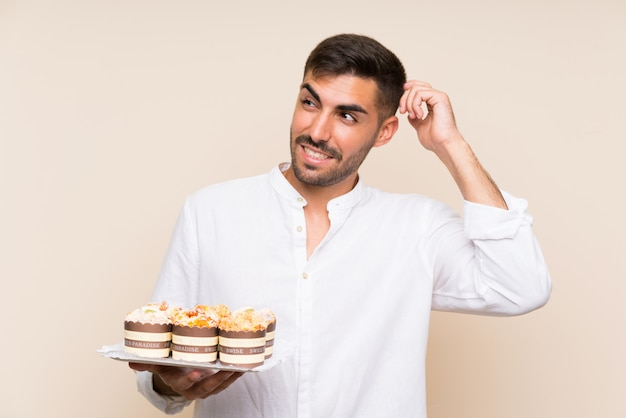 Handsome man holding muffin cake over isolated wall having doubts and with confuse face expression
