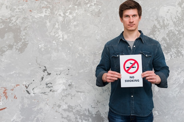 Handsome man holding no smoking banner standing near weathered wall