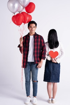 The handsome man holding olorful balloon in hand,looking straight.beside back side of woman showing small red heart paper cutted in hands,romantic couple