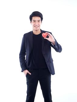 白に赤いプラスチックのハートを保持しているハンサムな男。バレンタインデーのコンセプト