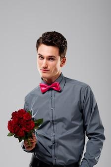 赤いバラを持っているハンサムな男