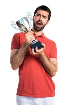Uomo bello che tiene un trofeo