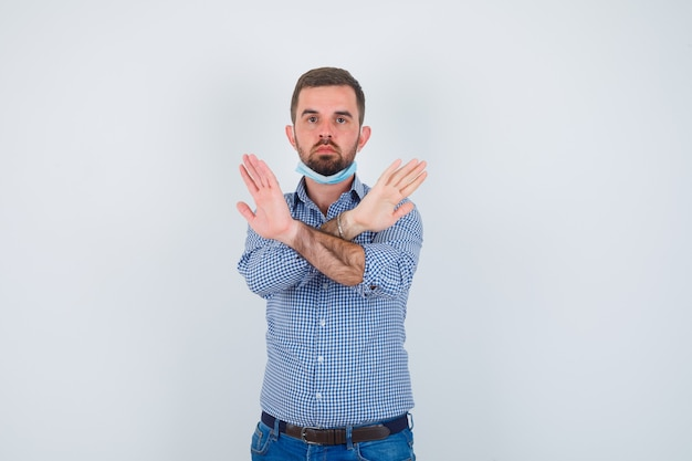 Uomo bello che tiene due braccia incrociate, non gesticolando alcun segno mentre si tiene la maschera sotto il mento in camicia, jeans, maschera e sembra serio. vista frontale.