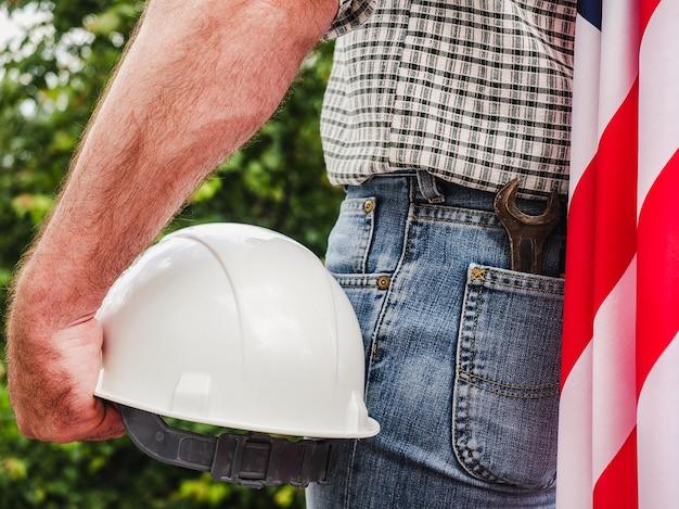 木々、青い空と夕日を背景に米国旗と建設用ヘルメットを保持しているハンサムな男。後ろからの眺め。労働と雇用の概念