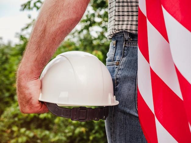 木の背景に米国旗と建設用ヘルメットを保持しているハンサムな男