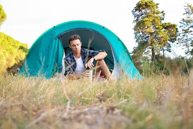 お茶と魔法瓶を保持し、テントに座っているハンサムな男。自然でリラックスし、芝生で楽しんでキャンプする白人男性ハイカー。観光、冒険、夏休みのコンセプトをバックパッキング