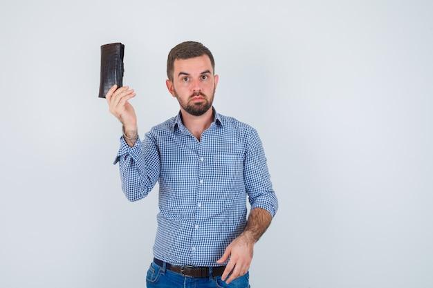 シャツ、ジーンズで財布を保持し、真剣に見えるハンサムな男、正面図。