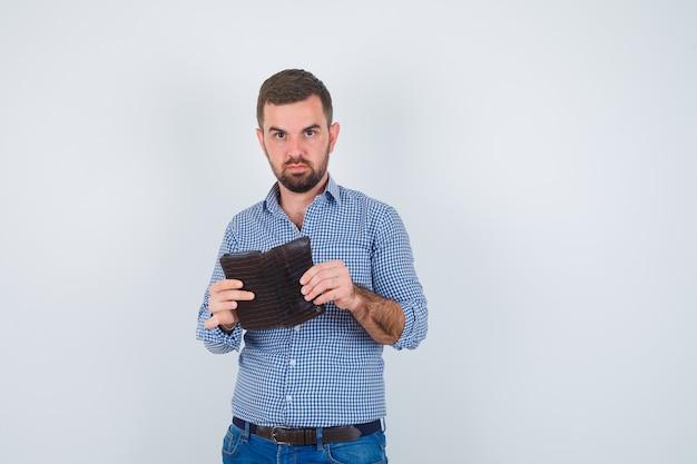 Uomo bello che tiene il portafoglio in camicia, jeans e guardando serio, vista frontale.