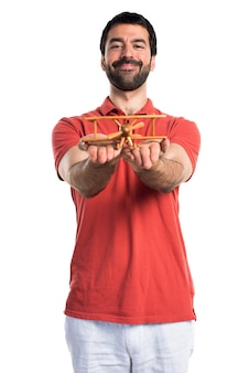 Handsome man holding a wooden toy airplane
