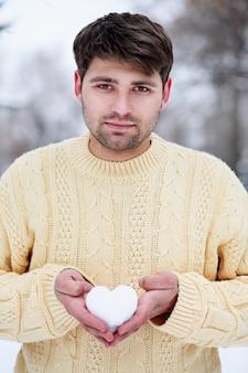 Красивый мужчина держит сердце из снега