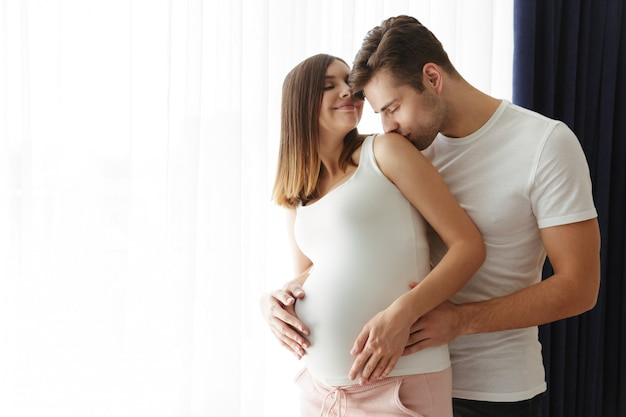 Handsome man hug his lovely pregnant wife indoors at home