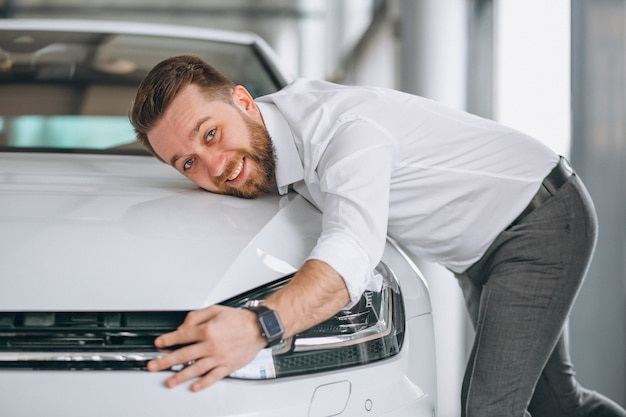 Handsome man hugging a car in a showroom