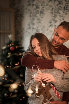 Handsome man hugging cheerful woman in sweaters near christmas tree