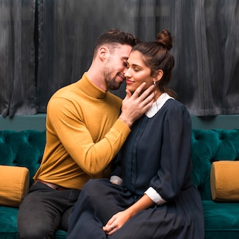 Handsome man hugging cheerful young woman on settee
