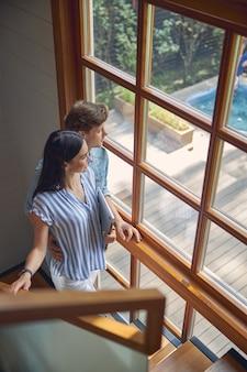 그들은 파노라마 창 근처 계단에 서있는 동안 그의 여자 친구를 포옹하는 잘 생긴 남자