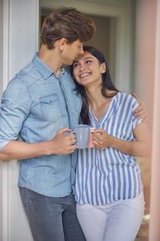 그들은 차 한잔에 아름다운 하루를 즐기는 동안 그의 웃는 아가씨를 포옹 잘 생긴 남자