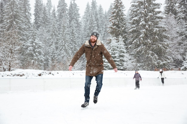 Handsome man ice skating outdoors with snow