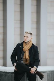 건물 앞 돌에 앉아 갈색 스카프와 검은 겨울 복장에 잘 생긴 남자