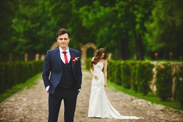신부 정장에 잘 생긴 남자가 그녀의 신부와의 만남을 기다리고 있습니다. 결혼식 전에 몇