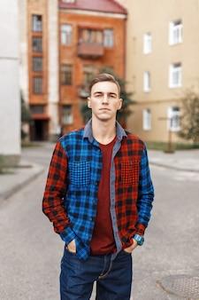 建物の市松模様のシャツを着たハンサムな男