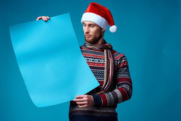 クリスマスの青いモックアップポスタースタジオポーズでハンサムな男