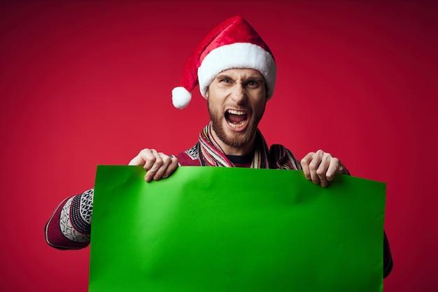 緑のモックアップ赤の背景を持つクリスマス帽子のハンサムな男。高品質の写真