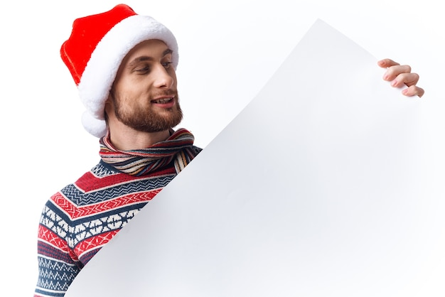 白いモックアップポスターのクリスマス帽子をかぶったハンサムな男クリスマスコピースペーススタジオ