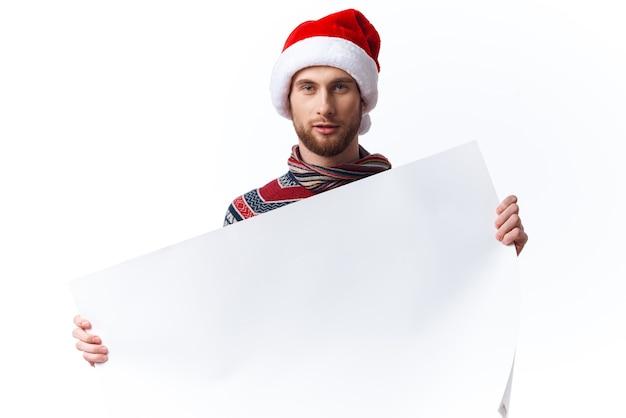 白いモックアップポスタークリスマスライトの背景を持つクリスマス帽子のハンサムな男。高品質の写真